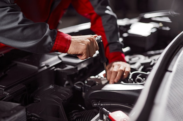 Mechanik naprawiający silnik samochodowy w warsztacie