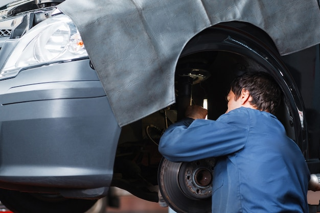 Mechanik naprawiający układ zawieszenia samochodu