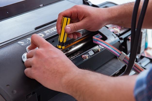 Mechanik naprawiający uszkodzoną drukarkę kolorową
