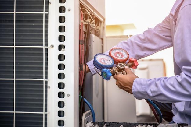 Mechanik naprawy powietrza za pomocą urządzeń pomiarowych do napełniania fabrycznych klimatyzatorów przemysłowych.