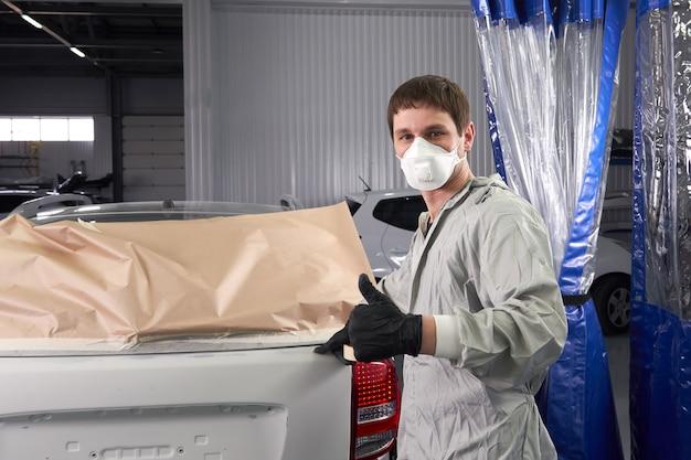 Mechanik obejmujący samochód przed malowaniem w serwisie samochodowym