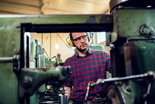 Mechanik obsługuje maszynę do cięcia przekładni w fabryce