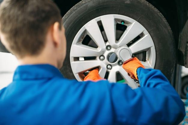 Mechanik odkręca koło samochodu, serwis opon.
