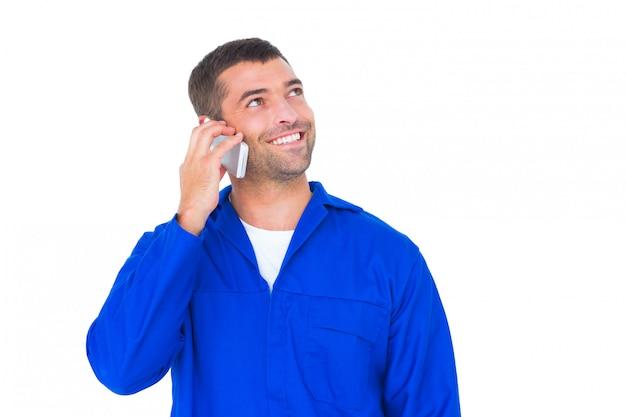 Mechanik patrząc w górę podczas rozmowy na telefon komórkowy