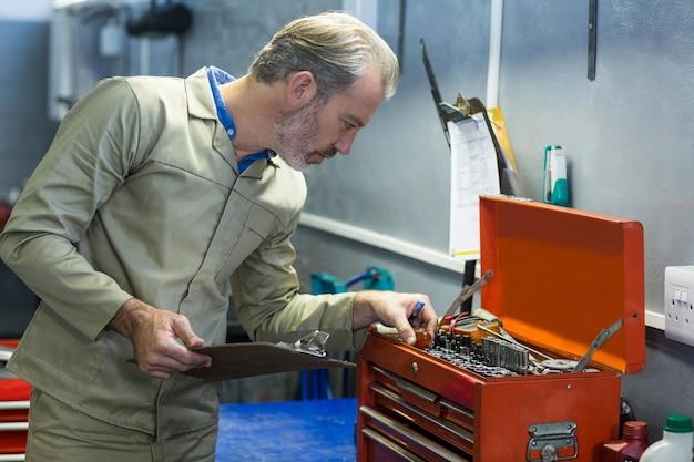 Mechanik patrząc w skrzynce narzędziowej
