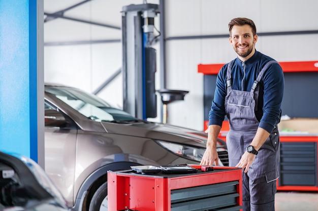 Mechanik pchający pudełko z narzędziami i przygotowujący się do naprawienia problemu z samochodem podczas spaceru po salonie samochodowym.