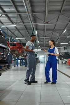 Mechanik płci męskiej i żeńskiej dokonuje przeglądu silnika, serwisu samochodowego