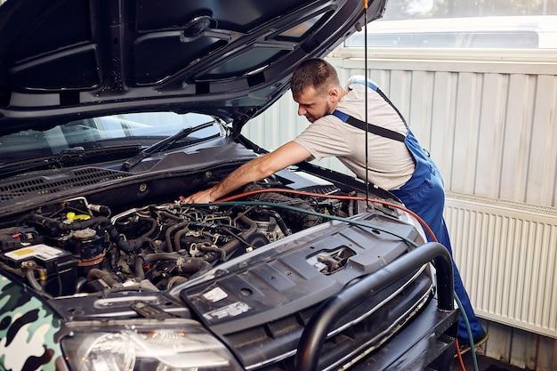 Mechanik podłącza system klimatyzacji do serwisu samochodowego