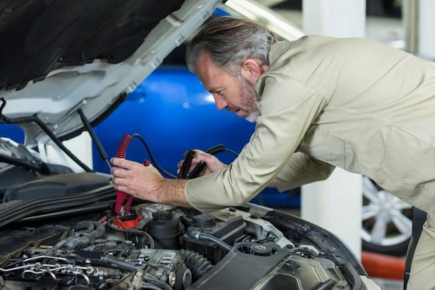Mechanik podłączanie kabli skoczka do akumulatora samochodowego