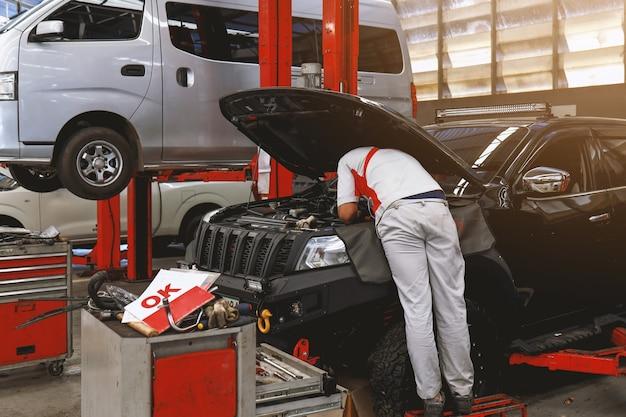 Mechanik pracujący przy konserwacji samochodu z miękkim ogniskiem i nad światłem w
