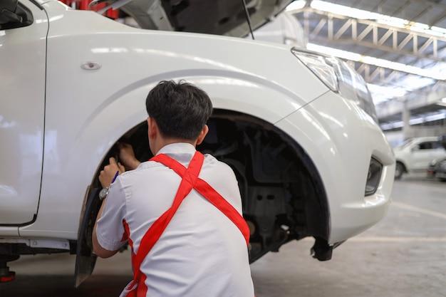 Mechanik pracujący przy konserwacji samochodu z miękkim ogniskiem i światłem w tle