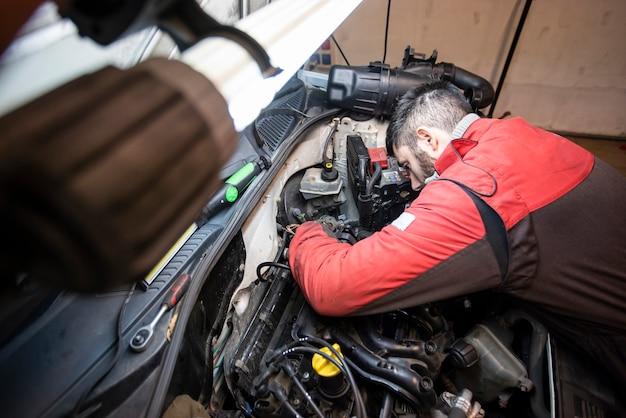 Mechanik pracujący przy silniku w warsztacie