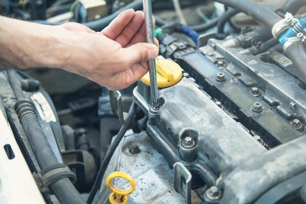 Mechanik pracujący w silniku samochodowym. naprawa samochodów, centrum serwisowe