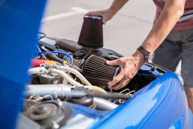 Mechanik pracuje przy samochodzie, wymieniając filtr powietrza dolotowego cylindra