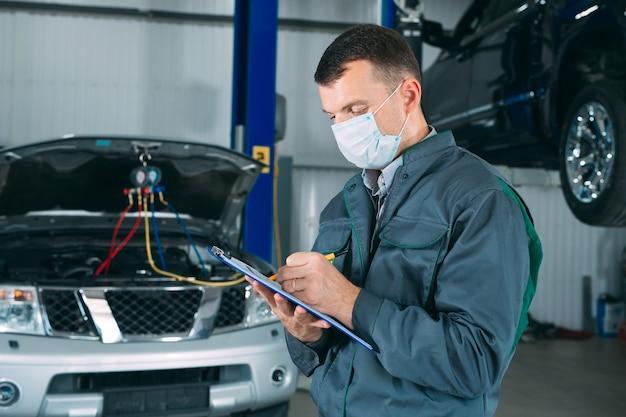Mechanik prowadzący rejestr samochodowy w schowku w warsztacie.