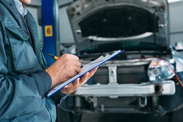 Mechanik prowadzący rejestr samochodowy w schowku w warsztacie