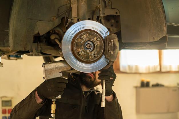 Mechanik przeprowadza wymianę hamulców samochodu w warsztacie