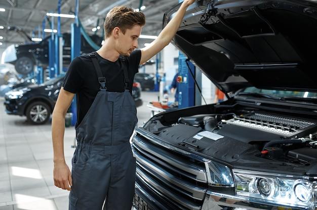Mechanik przy otwartej masce, widok z dołu, serwis samochodowy. garaż do naprawy pojazdów, mężczyzna w mundurze, wnętrze stacji samochodowej