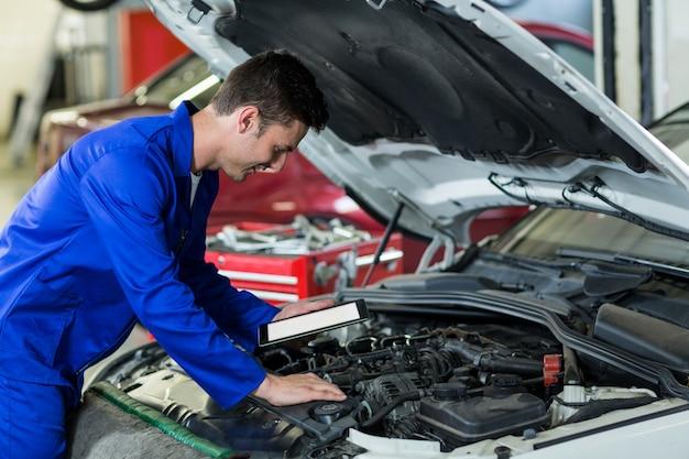 Mechanik przy użyciu cyfrowego tabletu podczas serwisowania silnika samochodu