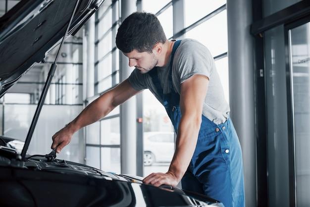 Mechanik ręce sprawdzanie przydatności samochodu w otwartej pokrywie, z bliska.