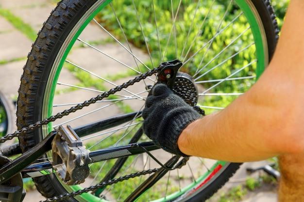 Mechanik rowerowy mężczyzna naprawia rower w warsztacie rowerowym odkryty ręka rowerzysty rowerzysta bada ...