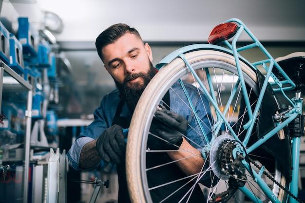 Mechanik rowerowy młody broda naprawa rowerów w warsztacie.