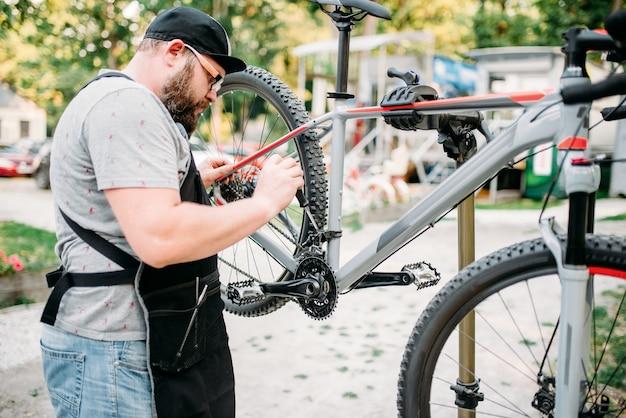 Mechanik rowerowy naprawia przednią dźwignię zmiany biegów. warsztaty rowerowe plenerowe. mocowanie roweru na stojaku