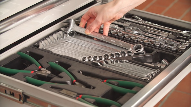 Mechanik samochodowy bierze odpowiedni klucz z zestawu narzędzi, naprawy samochodu, naprawy samochodu
