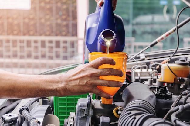 Mechanik samochodowy dodaje olej do silnika, przemysłu motoryzacyjnego i koncepcji warsztatów.