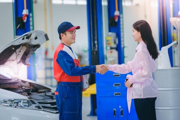 Mechanik samochodowy i klientka rozmawiają i trzymają się za ręce, aby naprawić samochód dziewczynki