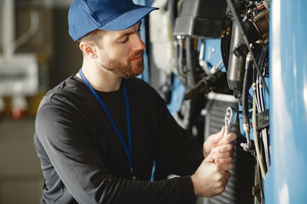 Mechanik samochodowy naprawia niebieski samochód w garażu za pomocą narzędzi