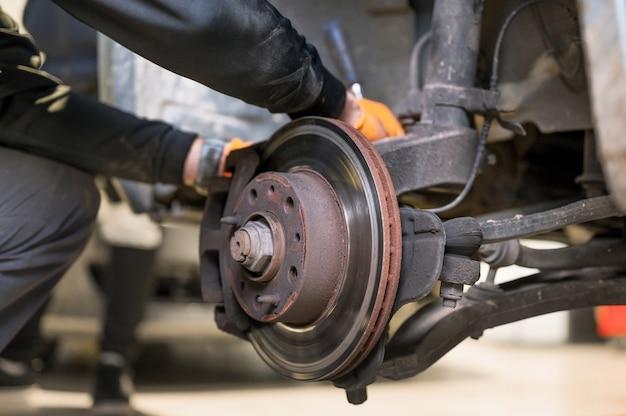Mechanik samochodowy naprawy klocków hamulcowych z bliska.