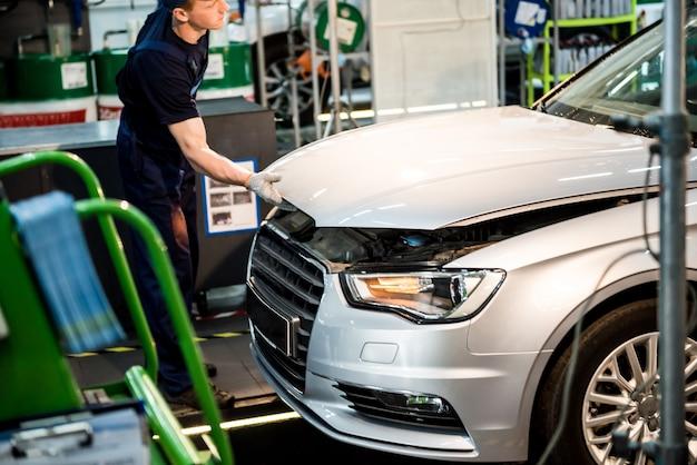 Mechanik samochodowy naprawy silnika na stacji obsługi. naprawa samochodów.