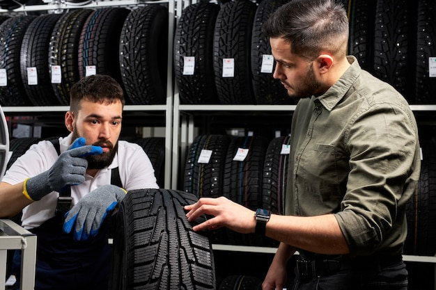 Mechanik samochodowy opowiada młodemu klientowi o zaletach opon samochodowych, mężczyzna przyszedł kupić nową oponę do swojego samochodu, rozmawia na stoisku i sprawdza produkt
