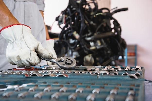 Mechanik samochodowy pracujący z kluczem nasadowym silnik samochodowy niewyraźne tło, koncepcje usług konserwacji i naprawy