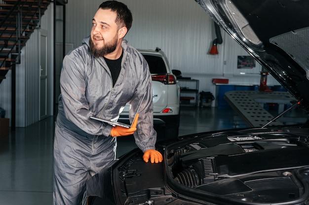 Mechanik samochodowy pracujący z laptopem w auto repair service sprawdzający silnik samochodu