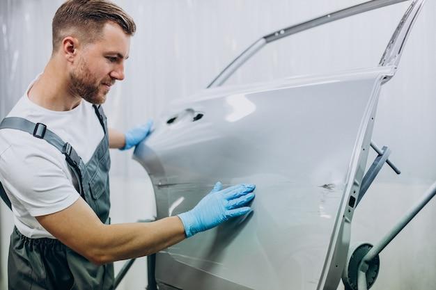 Mechanik samochodowy przygotowujący skrzydło samochodu przed malowaniem