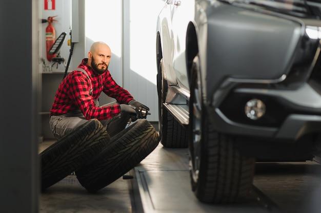 Mechanik samochodowy przykręcający koło samochodu podniesionego samochodu