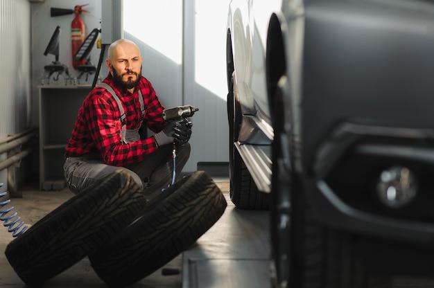 Mechanik samochodowy przykręcający lub odkręcający koło podniesionego samochodu
