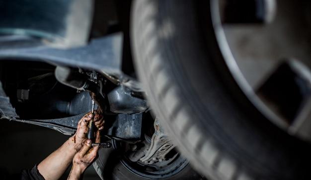 Mechanik samochodowy robi naprawy, konserwacja wymiany oleju do auta na podnośniku hydraulicznym, serwis samochodowy