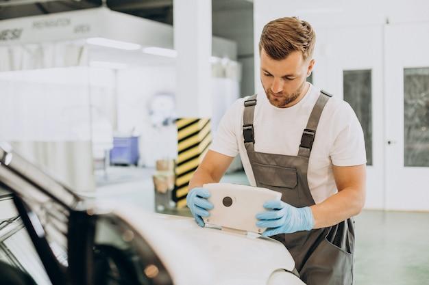 Mechanik samochodowy skanujący lakier samochodowy za pomocą specjalnego wyposażenia