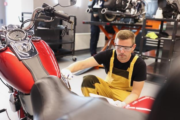 Mechanik samochodowy sprawdza stan techniczny motocykla w warsztatowym serwisie gwarancyjnym motocykli