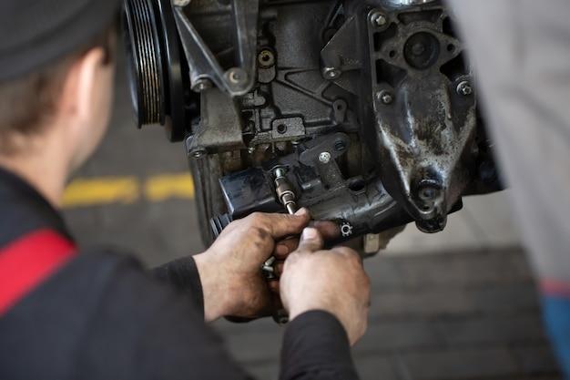 Mechanik samochodowy sprawdzający silnik spalinowy
