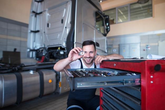 Mechanik samochodowy stoi przy wózku narzędziowym z częścią zamienną do serwisu samochodów ciężarowych