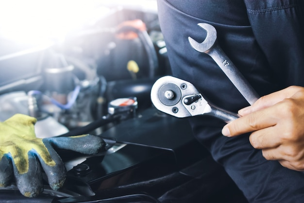 Mechanik samochodowy trzymający klucz w warsztacie samochodowym
