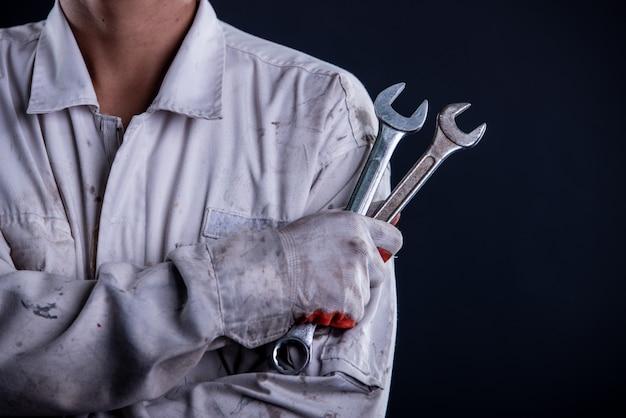 Mechanik samochodowy w białym mundurze stojącym trzymając klucz