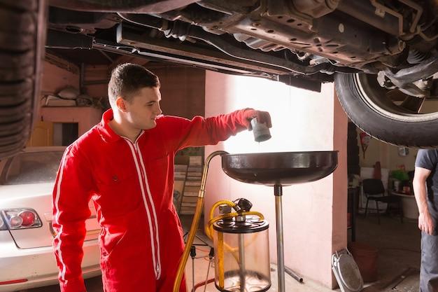 Mechanik samochodowy w mundurze pracujący pod podniesionym samochodem i wymieniający olej silnikowy
