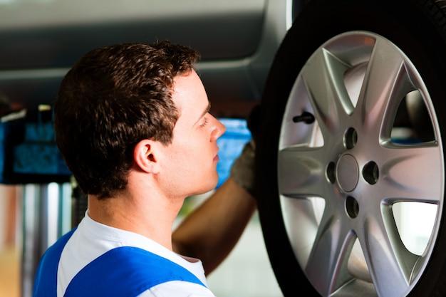 Mechanik samochodowy w warsztacie zmienia oponę