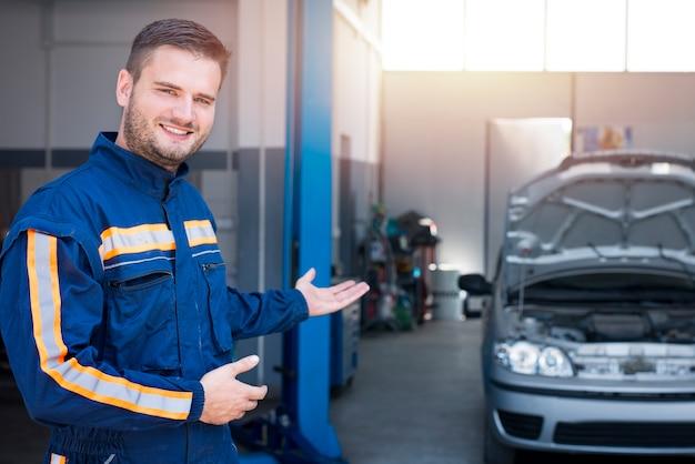 Mechanik samochodowy wita klientów w swoim warsztacie.