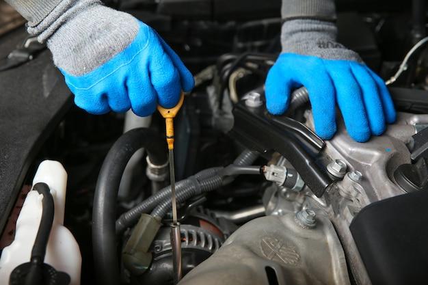Mechanik samochodowy wyciąga prętowy wskaźnik poziomu oleju z silnika samochodu